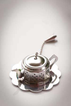 infuser: Metallic tea strainer infuser isolated over gray background