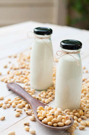 Soy milk [Soya milk ] in  glass bottle with soy pods on white wooden background, healthy drink