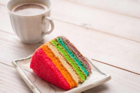 木製のテーブルの上の白いティーカップとの虹のケーキ