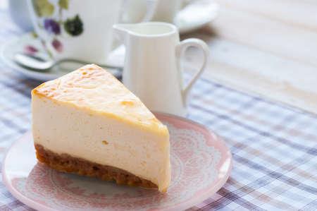 紅茶のカップを持つニューヨーク様式のチーズケーキのスライス