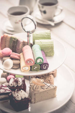 afternoon tea: cakes and macaroons on two tiered tray with teapot and cup background