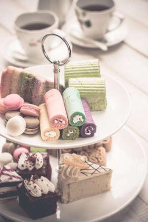 comida inglesa: pasteles y macarrones en dos bandejas con gradas con tetera y la taza de fondo Foto de archivo