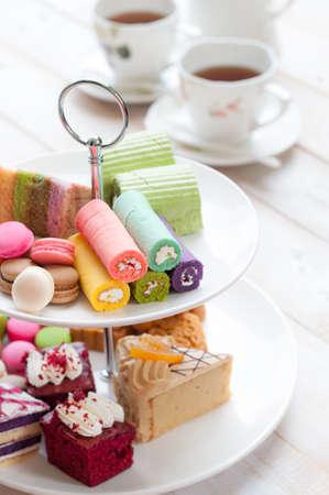 ケーキとマカロンのティーポットとカップの背景を持つ 2 つの階層型トレイ