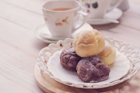 cream puff: cream puff (Choux Cream) with a cup of tea on white wooden board, vintage tone Stock Photo