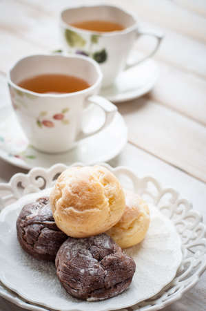 cream puff: cream puff (Choux Cream) with a cup of tea on white wooden board