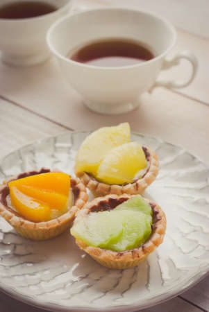 short crust pastry: fruit tart with tea cup on wooden board Stock Photo