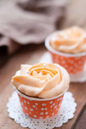 afternoon fancy cake: orangr cupcake on wooden board.
