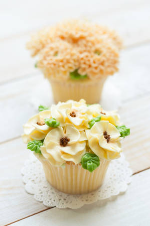 sugarcraft: home made sponge cupcakes with flowers buttercream frosting on white wooden background.