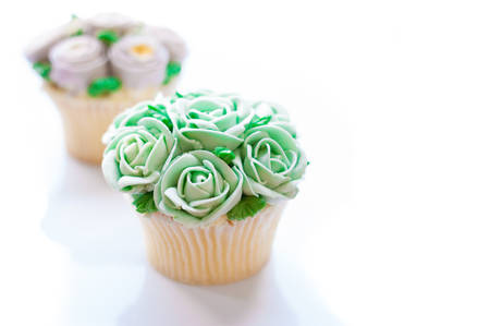 sugarcraft: home made sponge cupcakes with flowers buttercream frosting on wooden background. Afternoon tea concept