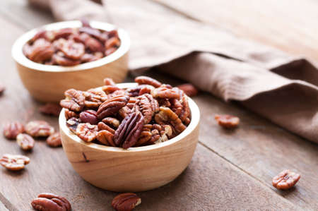 bowel: Pecan nuts in wooden bowel on wooden background with copy space for text