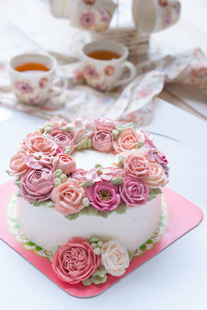 Gorgeous cake covered in roses made of butter cream icing on white wooden background, Afternoon tea set