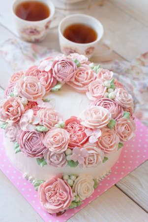Splendida torta ricoperta di rose fatte di burro crema crema su sfondo bianco in legno Archivio Fotografico - 81446013