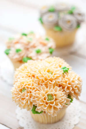 home made sponge cupcakes with flowers buttercream frosting on white wooden background.