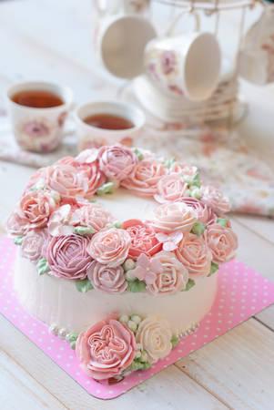 木製の白い背景の上のアイシング バター クリームのバラで覆われた豪華なケーキ