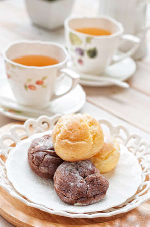 cream puff(Choux Cream) with a cup of tea on white wooden board, afternoon tea relaxing time concept 版權商用圖片