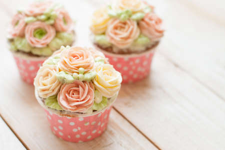 gum paste: home made sponge cupcakes with flowers buttercream frosting on white wooden background.