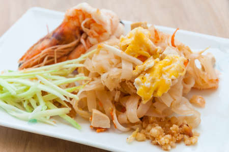 Seafood pad Thai dish of stir fried rice noodles on a square white plate