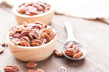 Pecan nuts in wooden bowel on wooden background with copy space for text