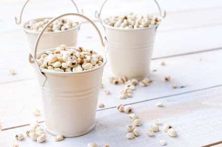 energy healing: Jobs tears in white bucket on wooden board, healthy food