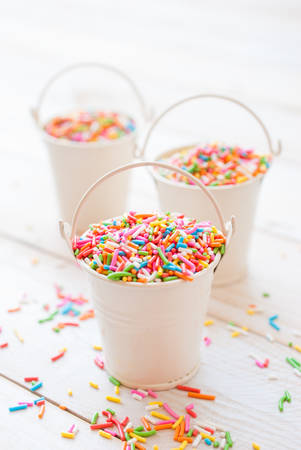 Sugar sprinkle dots, decoration for cake and bekery, a lot of sprinkles in a bucket on white wooden board background Stock Photo