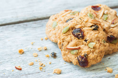 Pumpkin, oat cookies with cranberries, almond on wooden background