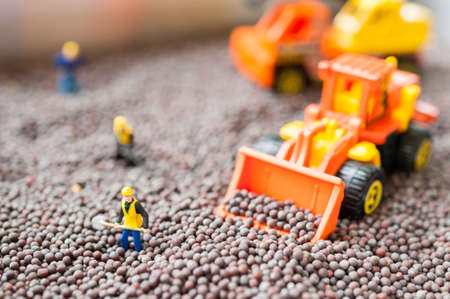 miniature people with bull dozer and Excavator toy with black mustard Stock Photo