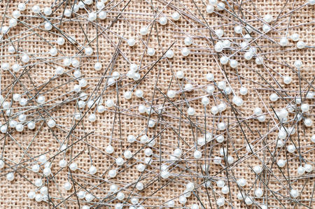 Sewing pins on burlap background