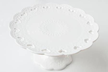 white ceramic cake stand on grey background