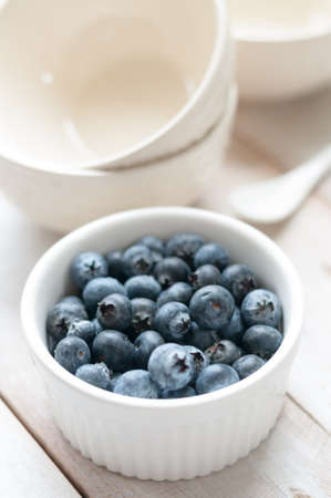 Blueberries on white ramekin placed on white wooden board Stock Photo