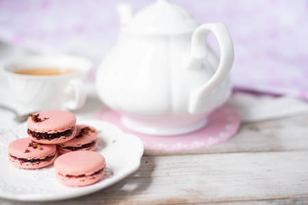 Pink macaroon with teapot on wooden background