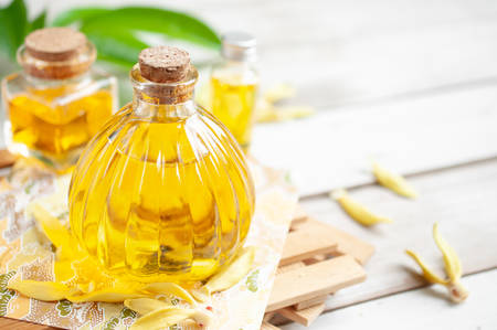 Ylang ylang oil in bottles on wooden background Stock Photo