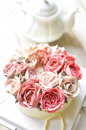 Pink Buttercream flower cake with teapot on wooden background Standard-Bild