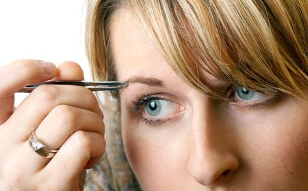 plucking: woman is plucking eyebrows, separate on white