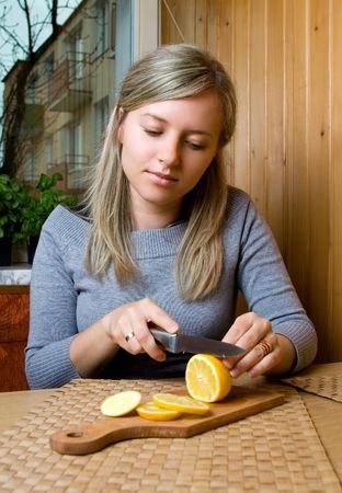 ingradient: pretty woman cuts lemon in kitchen