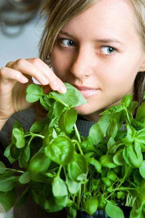 pretty woman smell fresh basil Stock Photo