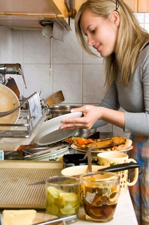 dirty dishes: woman washing plates in kitchen Stock Photo
