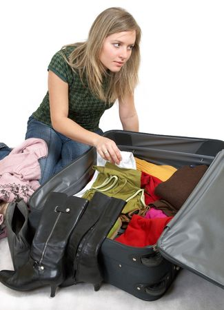 girl is packing clothes i bag, separate on white