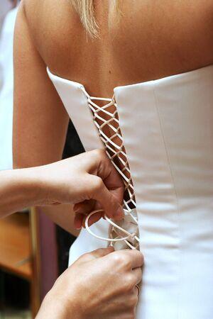 woman puts on beautiful white wedding dress Stock Photo