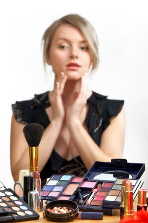 young beautiful woman is making up for itself in front of a mirror