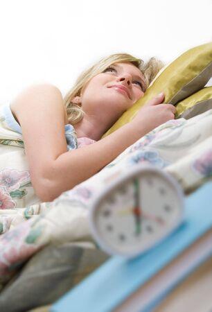 despertador: Somnoliento mujer apaga despertador  Foto de archivo