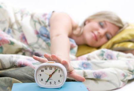 sleepy woman shuts off  alarm clock