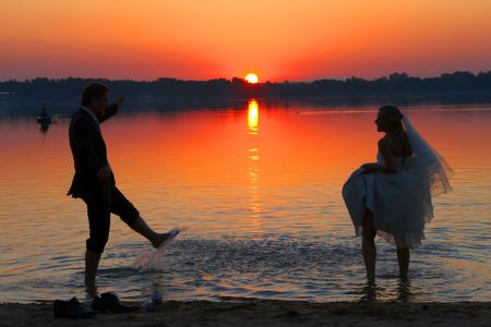 the young couple is standing after the marriage ceremony on the beach and cuddling