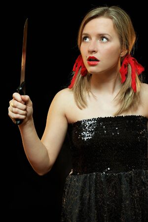 Beautiful woman with knife. She is terrified.  Black background.