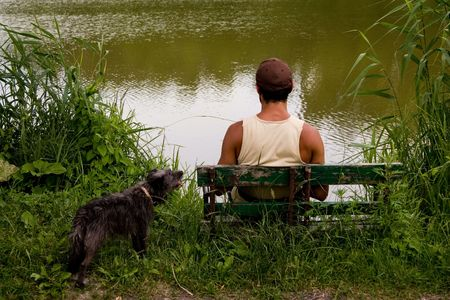 suntanned: man is sitting on bench on lake
