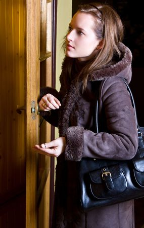 woman is standing in doorway with key in palm