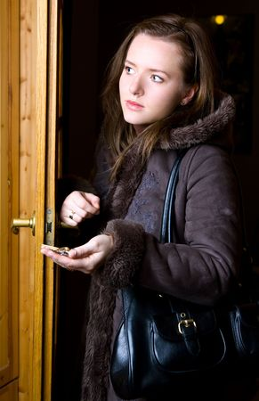 woman is standing in doorway with key in palm photo