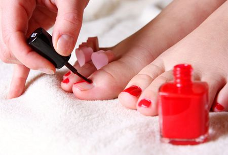 foots: red nail polish on her foot fingers Stock Photo
