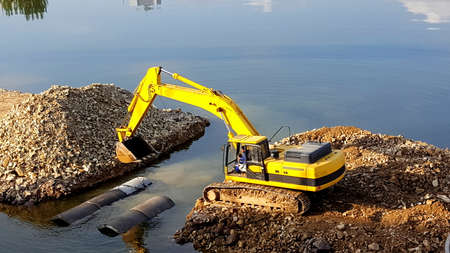 Strong yellow excavator machine works at river