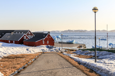greenlandic: Road to the old harbor with icebergs in a fjord in the background, Nuuk, Greenland Stock Photo