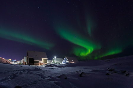 nuuk: Row of cabins and green Northern lights in a suburb of Nuuk Stock Photo